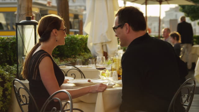 stockvideo's en b-roll-footage met ms couple feeding each other and toasting with red wine in outdoors restaurant / venice,veneto - mid volwassen koppel