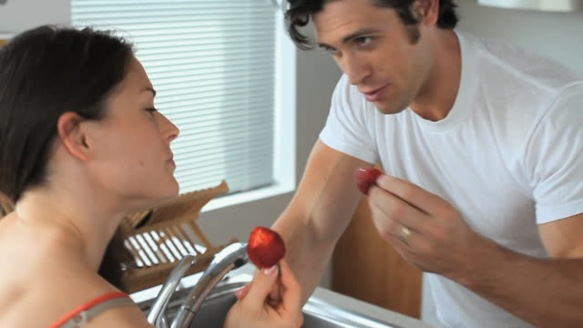 ms couple feeding each other strawberries in kitchen, jersey city, new jersey, usa - nutrire video stock e b–roll