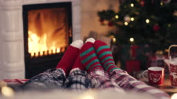 Couple feet in cozy christmas woolen socks near fireplace with decorated xmas tree and tee cup in background