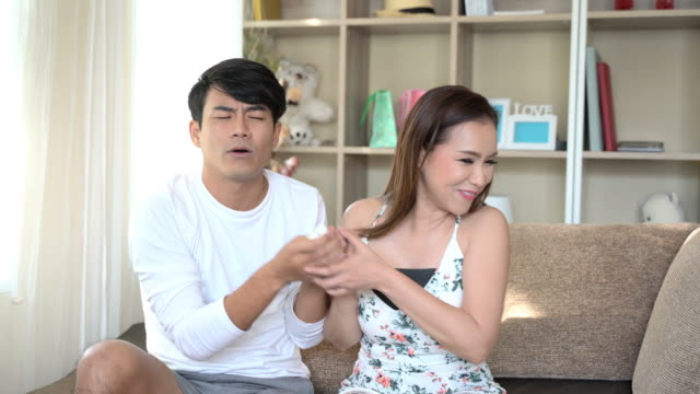 vídeos de stock, filmes e b-roll de casal lutando pela televisão remoto - controle