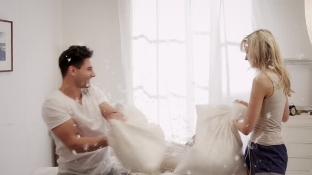 couple fighting with pillows in bedroom - pillow fight stock videos & royalty-free footage