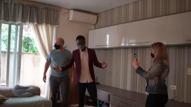 vidéos et rushes de maison de tournage de couple montrée par un agent immobilier - port d'un masque de protection - montrer