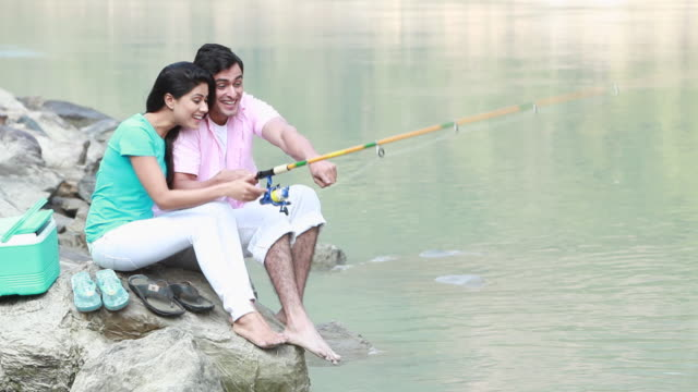 Couple fishing at river bank