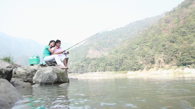 vídeos y material grabado en eventos de stock de couple fishing at river bank - nevera portátil