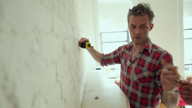 CU R/F Couple fixing up house interior, measuring wall with tape / Brooklyn, New York City, USA
