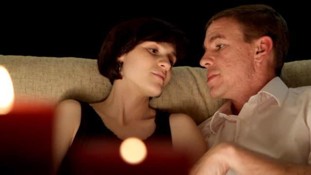 coppia flirtare, a lume di candela - whispering video stock e b–roll