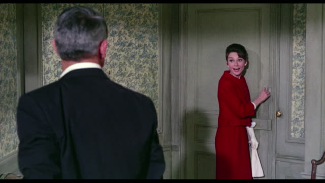1963 couple (cary grand and audrey hepburn) flirt together in joining hotel rooms  she teasingly screams so he comes running to her rescue and she traps him in her room saying, 'got you!' - audrey hepburn stock videos & royalty-free footage