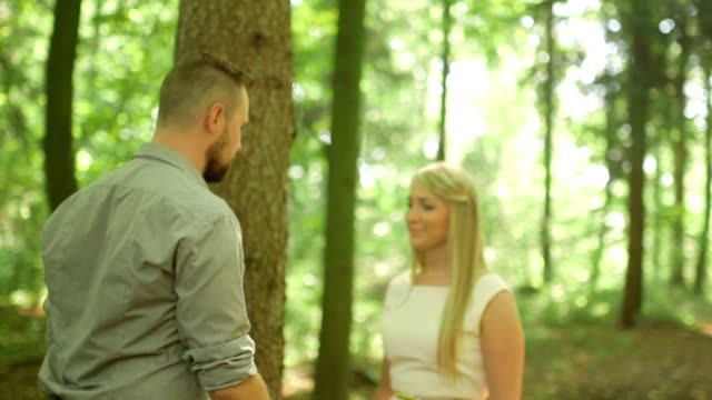 MEDIUM SHOT TILT DOWN DOLLY SHOT Couple flirting in forest on sunny day
