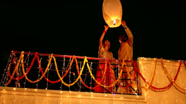 couple flying paper lantern in diwali festival, delhi, india - paper lantern stock videos and b-roll footage