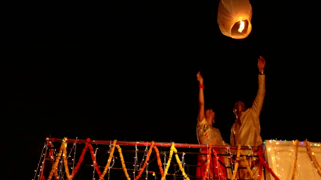 couple flying paper lantern in diwali festival, delhi, india - fun stock videos & royalty-free footage
