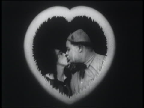 b/w 1916 couple framed by heart kissing + smiling at camera - 1910 stock videos & royalty-free footage