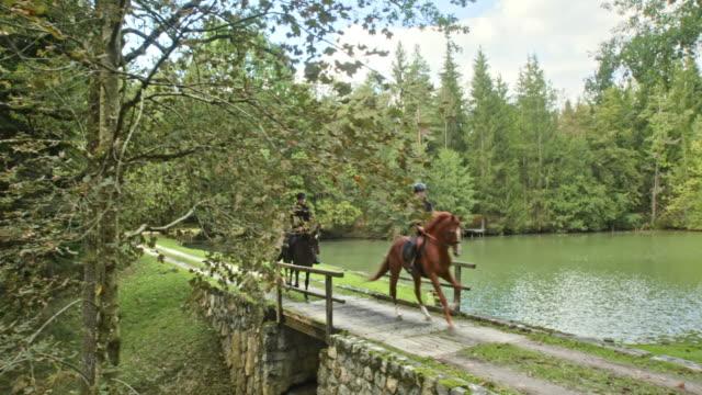 vídeos de stock, filmes e b-roll de cs casal galopando em seus cavalos através de uma ponte - cavalgar