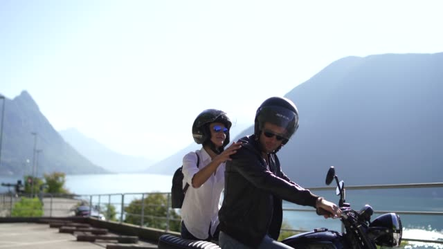 vídeos de stock e filmes b-roll de couple getting on a motorcycle next to a lake on a sunny day - capacete moto