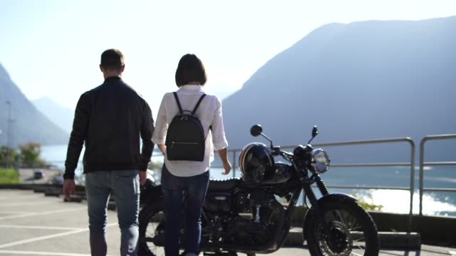 couple getting on a motorcycle next to a lake on a sunny day - casco da motociclista video stock e b–roll