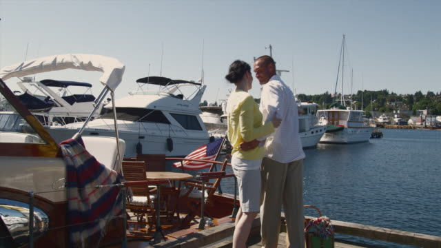 ws couple getting on boat with picnic basket / seattle, washington, usa - picnic basket stock videos and b-roll footage