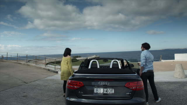 SLO MO WS Couple getting out of convertible car and looking out over ocean, Bondi Beach / Sydney, Australia