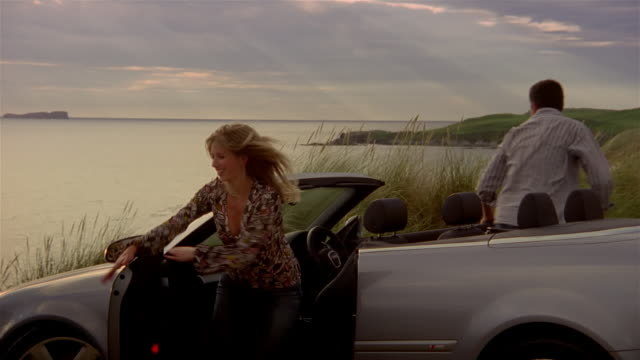couple getting out of convertible parked on promontory and running down to shore of loch / scotland - 降り立つ点の映像素材/bロール