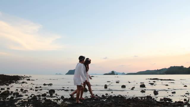 vídeos de stock, filmes e b-roll de garota do casal desfrutar e relaxar na praia da rocha - brincadeira de pegar