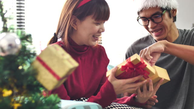 Couple Giving and opening Christmas gifts in living room on Christmas Day