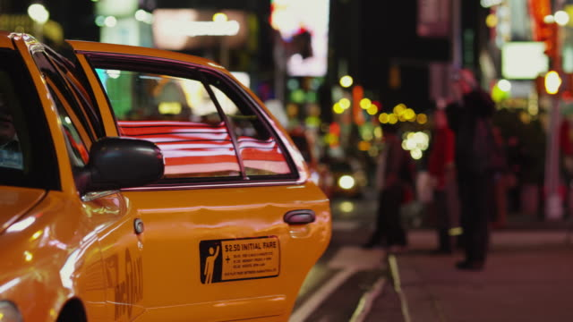SLO MO MS Couple hailing cab in Times Square at night / New York City, New York State, USA