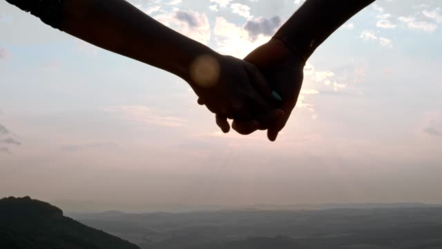 a couple hand-holding and walking towards the sunset, slow motion, close up - human hand stock videos & royalty-free footage