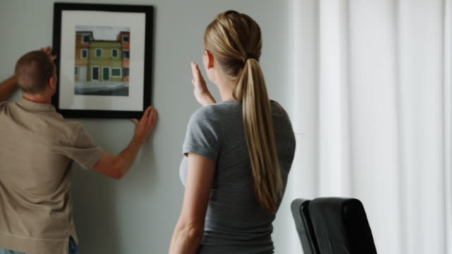 couple hanging a picture on the wall - see other clips from this shoot 1418 stock videos & royalty-free footage