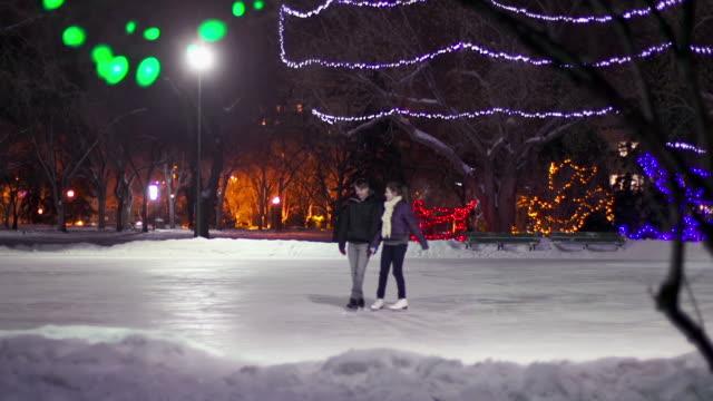vídeos de stock e filmes b-roll de casal tem de data em um inverno noite. - patinagem no gelo