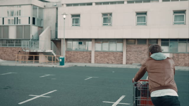 vídeos de stock, filmes e b-roll de casal haveing diversão com carrinho de compras - pushing