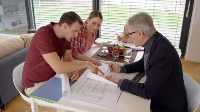 Couple having a meeting with an architect in their home