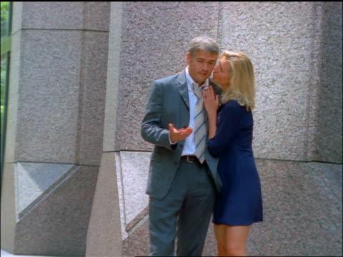 couple having argument on city street / woman pushes man + walks away - flickvän bildbanksvideor och videomaterial från bakom kulisserna