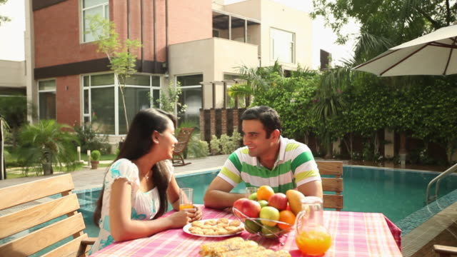 Couple having breakfast at poolside in the farm house