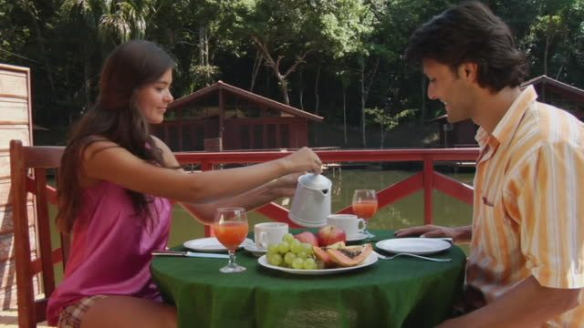 MS, Couple having breakfast by Amazonian river rustic resort, Manaus, Brazil