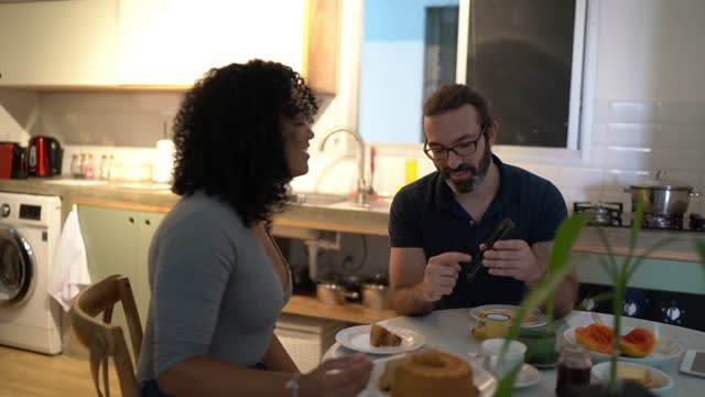 couple having breakfast together and using smartphone at home - breakfast stock videos & royalty-free footage