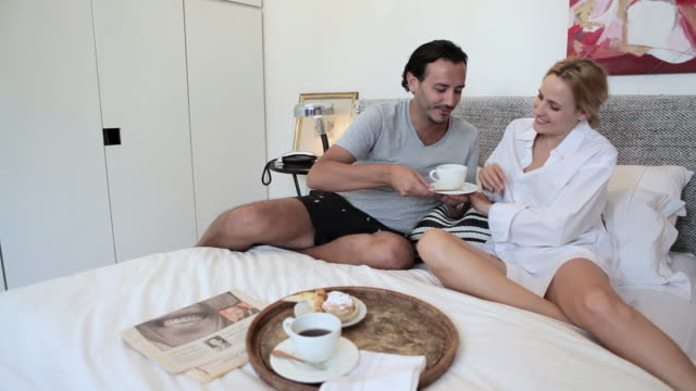 Couple having coffee and breakfast in bed