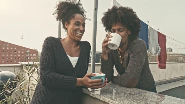 vídeos de stock, filmes e b-roll de casal tomando café no terraço - varanda