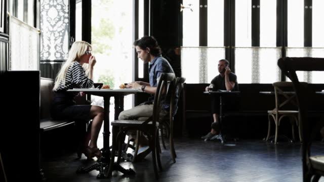 couple having coffee in cafe - コーヒーショップ点の映像素材/bロール