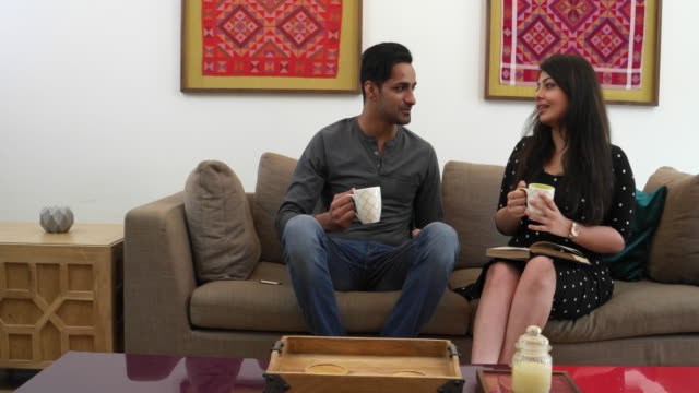 couple having coffee seated on a couch in a living room, dolly shot - indian couple tea stock videos & royalty-free footage