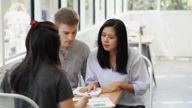 Couple having conversation discussing personal finance document loan contract, real estate purchase with sale represent.