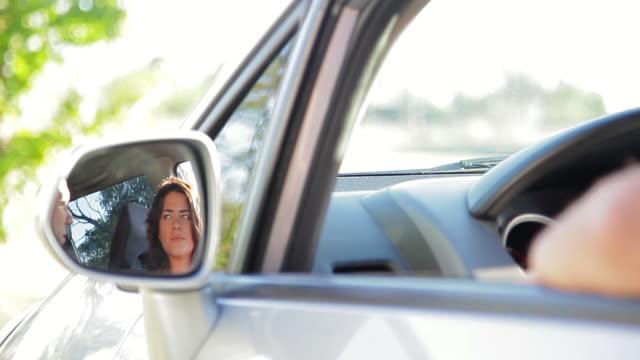 vídeos de stock e filmes b-roll de couple having conversation in car, reflected in side-view mirror - tremido