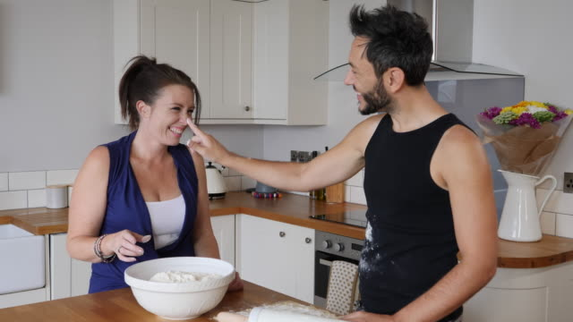 4k: couple having flour fight in kitchen - flour stock videos and b-roll footage