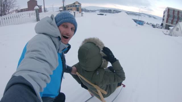 POV Couple having fun kick sledding through the town