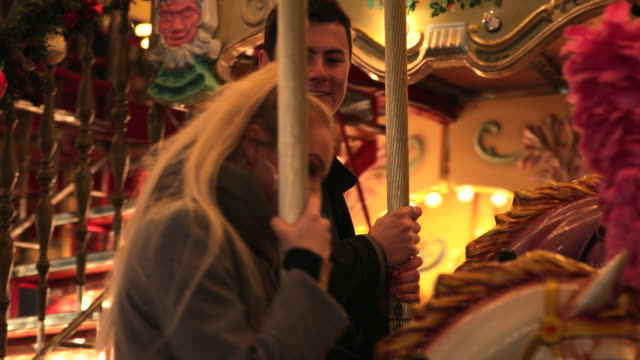 couple having fun on a carousel - roundabout stock videos & royalty-free footage