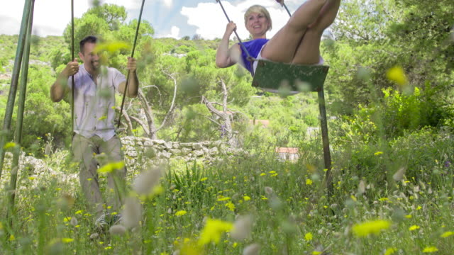 ls ds couple having fun on a swing - mid adult couple stock videos & royalty-free footage