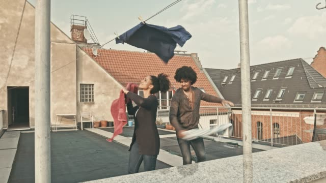 couple having fun putting the laundry to dry at terrace - washing line stock videos & royalty-free footage