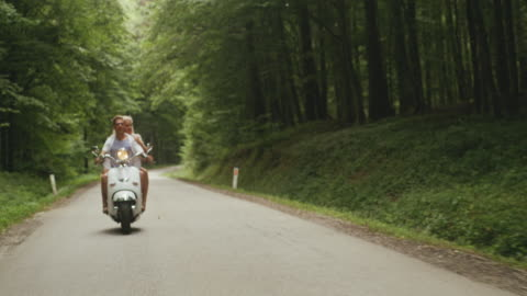 ws couple having fun riding a scooter through a forest - mid adult couple stock videos & royalty-free footage