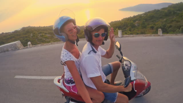 pov couple having fun riding a scooter - helmet stock videos & royalty-free footage