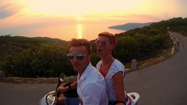 POV Couple having fun riding a scooter
