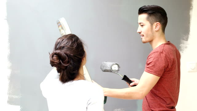 Couple having fun while painting wall in new home