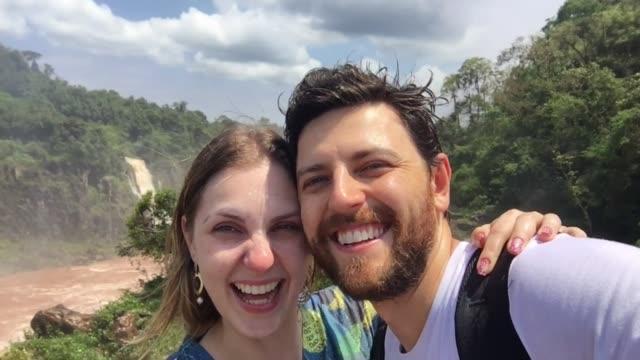 vidéos et rushes de couples s'amusant tout en prenant des selfies dans les chutes d'iguazu - enjoyment