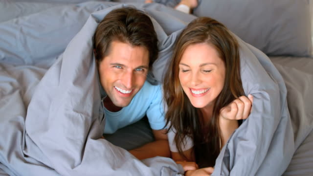 vídeos de stock, filmes e b-roll de couple having fun wrapped in their duvet - cor de cabelo